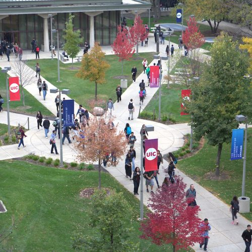aerial view of students walking through campus with skyline in background